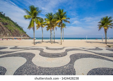 The most popular beach and a favorite holiday destination for tourists from all over the world. Famous Mosaic of Sidewalk and Palm Trees in Leme and Copacabana Beach in Rio de Janeiro, Brazil.