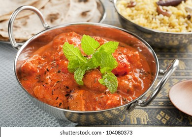 The most popular curry in the UK, chicken tikka masala, here served in a balti dish or karahi, garnished with mint, accompanied by pilau rice and chapatis.