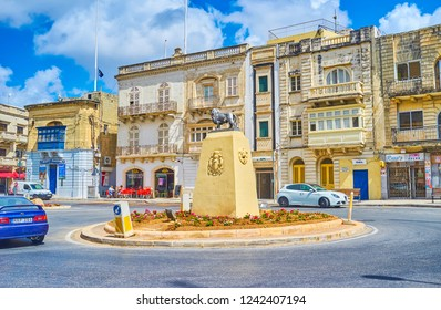 MOSTA, MALTA - JUNE 14, 2018: The statue of lion - the city symbol, in the middle of U-turn in busy Rotunda Square with old edifices on background, on June 14 in Mosta.