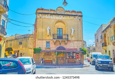 MOSTA, MALTA - JUNE 14, 2018: The beautiful edifice with pair of sculptures on its facade and shady cafe terrace on the ground floor, on June 14 in Mosta.