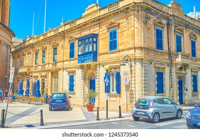 MOSTA, MALTA - JUNE 14, 2018: The beautiful historical edifice with blue window shutters and balcony neighbors with Basilica Rotunda, on June 14 in Mosta.
