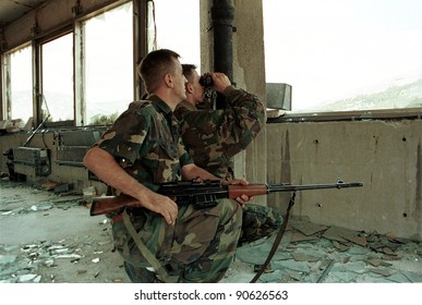 MOSTAR, BOSNIA - AUGUST 16: A Bosnian-Croat HVO sniper team peers out of a destroyed bank building at Bosnian-Muslim civilians on the east side of this divided city in Mostar, Bosnia on Aug 16, 1993.