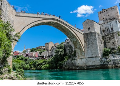 Mostar, Bosnia and Herzegovina - 16 May, 2018: Watched by tourists, local men have a tradition of jumping  from the famous bridge Stari Most in the picturesque old town