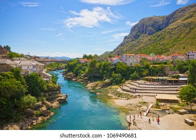 Mostar, Bosnia and Herzegovina - April 13, 2018: Tourists near Mostar river view on old town in spring.