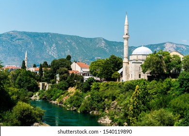 Mostar, Bosnia and Herzegovina - August 12, 2019: Koski Mehmed Pasha Mosque, mountains in background