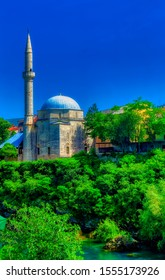 MOSTAR, BOSNIA AND HERZEGOVINA, June 07 2019: Old mosque located at bank of river Neretva in Mostar, Bosnia and Herzegovina.
