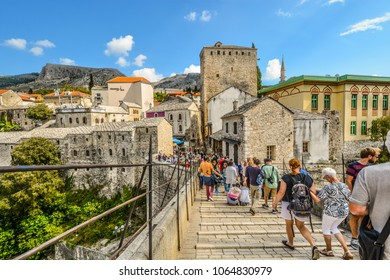Mostar, Bosnia and Herzegovina - October 1 2017: A crowd of tourists cross over the restored Mostar Bridge in the city of Mostar, Bosnia, as they make their way into the old town section.