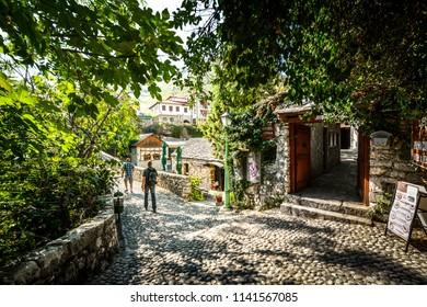 Mostar, Bosnia and Herzegovina - October 1 2017: Tourists walk a cobblestone path over a bridge in the medieval city of Mostar, Bosnia on an autumn morning.