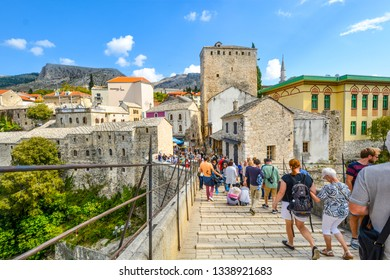 Mostar, Bosnia and Herzegovina - October 1 2018: A crowd of tourists cross over the restored Mostar Bridge in the city of Mostar, Bosnia, as they make their way into the old town section.