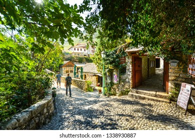 Mostar, Bosnia and Herzegovina - October 1 2018: Tourists walk a cobblestone path over a bridge in the medieval city of Mostar, Bosnia on an autumn morning.