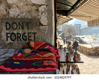 """MOSTAR, BOSNIA - JAN 26, 2018: """"Don't forget"""" message in Open Street touristic market in the old town, Mostar in Bosnia-herzegovina. The name Mostar itself means """"bridge-keeper."""""""