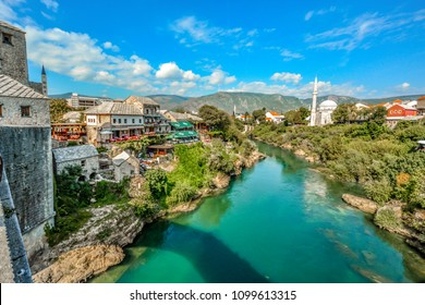 Mostar, Bosnia - October 1 2017: afes, minarets and mosques along the river Neretva in the old town of Mostar, Bosnia and Herzegovinia. Taken from the old Mostar Bridge mid afternoon