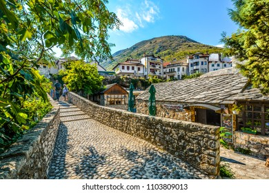 Mostar, Bosnia - October 1 2017: Tourists walk a cobblestone path over a bridge in the medieval city of Mostar, Bosnia on an autumn morning.