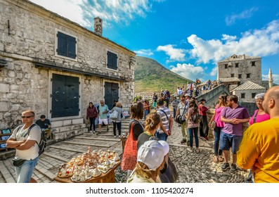 Mostar, Bosnia - October 1 2017: Tourists crowd the Mostar Bridge in the medieval city of Mostar, Bosnia and Herzegovina in early autumn as local Bosnians sell souvenirs and two men prepare for a dive