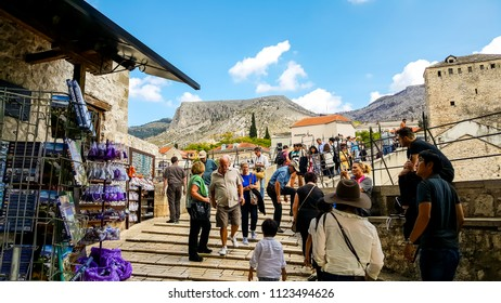 Mostar, Bosnia - October 1 2017: Tourists crowd the Mostar Bridge in the medieval city of Mostar, Bosnia and Herzegovina in early autumn as local Bosnians sell souvenirs and a diver prepare for a dive