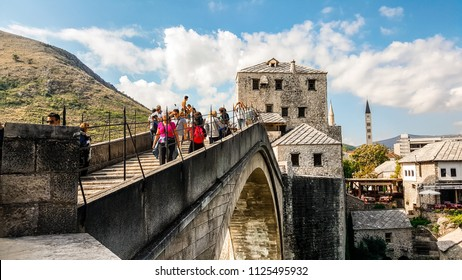 Mostar, Bosnia - October 1 2017: Tourists cross the Mostar Bridge in the medieval city of Mostar, Bosnia and Herzegovina in early autumn as local Bosnian prepares for a high dive