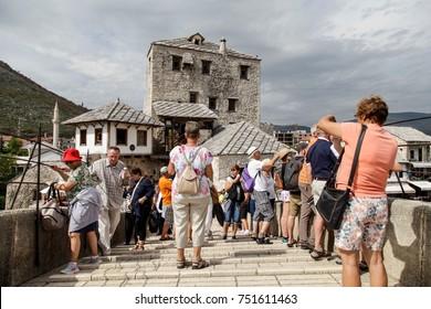 MOSTAR, BOSNIA - SEPTEMBER 16, 2015: Tourists on the old bridge in Mostar, Bosnia