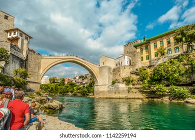 Mostar, Bosnia - September 29 2017: A Tourists watch as a Bosnian diver walks from the Neretva River in old town Mostar, Bosnia and Herzegovina after diving from the Stari Most, or old Mostar Bridge.
