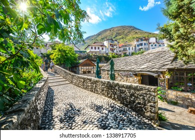 Mostar, Bosnia-Herzegovina - October 1 2018: Tourists walk a narrow cobblestone path over a bridge and past a cafe in the medieval city of Mostar, Bosnia on an autumn morning.