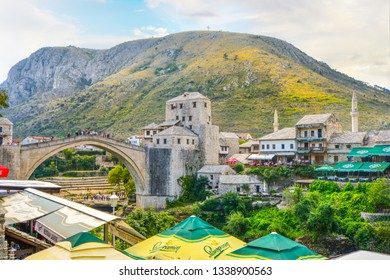 Mostar, Bosnia-Herzegovina - September 29 2018: The cross over Mostar on Hum Hill stands atop the mountain overlooking Old Town Mostar with the old bridge below and outdoor cafes with tourists