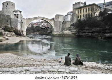 Mostar bridge in Bosnia and Herzegovina in winter. Family looking the bridge near the river. People crossing the bridge. The Neretva river.