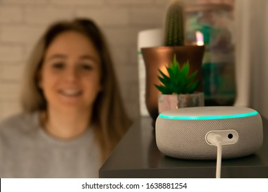 MOSTERTON ENGLAND FEBRUARY 2020 - Teenage girl talking to an Amazon Alexa Echo Dot. Smiling girl