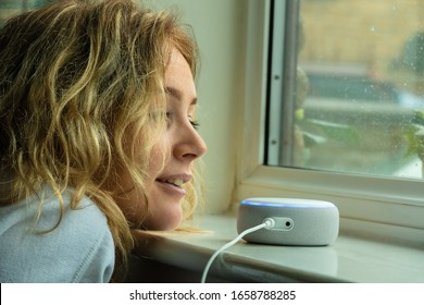 MOSTERTON ENGLAND FEBRUARY 2020 - Teenage girl talking to an Amazon Alexa Echo Dot by a window on a rainy day