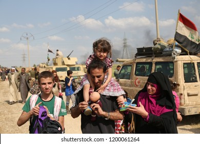 Mosul, Iraq - May 5,2017: A displaced family flees from Mosul, ISIS Caliphate territory, during coalition advance into the northwest of the city.