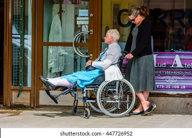 Motala, Sweden - June 21, 2016: Disabled senior lady in a wheelchair stretches her legs as she and her friend or helper waits outside a small shop in town. Real life situation.