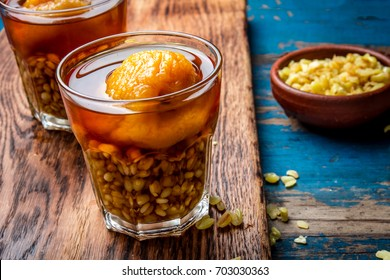 Mote con huesillo. Traditional Chilean drink made from cooked husked wheat and dried peach on wooden board, rustic blue background.