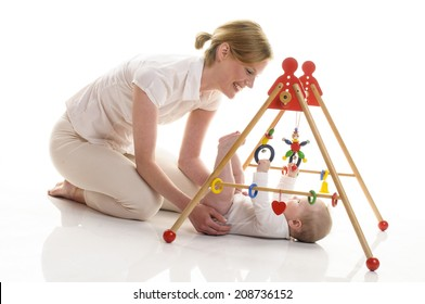 Mother and 6 month old daughter playing together on the floor with wooden toys and play bow, isolated against white background.