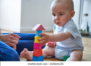 Mother With 8 Month Old Baby Son Learning Through Playing With Coloured Wooden Blocks At Home