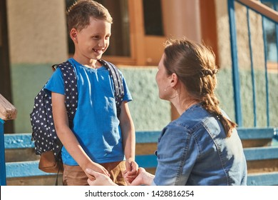 mother accompanies the child to school. mom encourages student accompanying him to school. a caring mother looks tenderly at her son going to school. positive boy happy to go to school