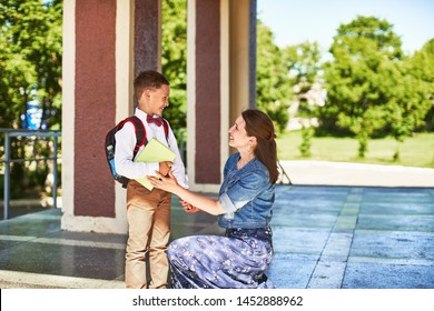 mother accompanies the child to school. mom encourages the student to accompany him to school. caring mother looks tenderly at her son going to school.positive boy having fun going to primary school