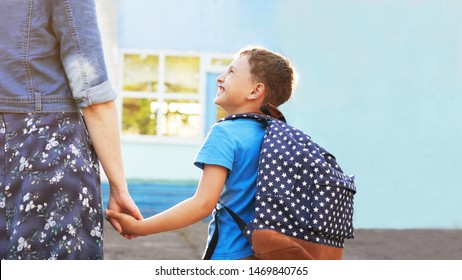 mother accompanies the child to school. mom encourages the student to accompany him to school. a caring mother looks tenderly at her son going to school.positive boy having fun going to primary school