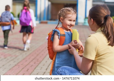 mother accompanies child to school. mom supports and motivates the student.caring mother with tenderness looks at her daughter,passes her book textbook.positive little girl fun going to primary school