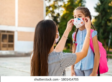 Mother adjusting mask to her kid before she goes to school