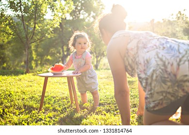 mother and a adorable baby enjoying a warm sunny day at the park,playing with watermelon