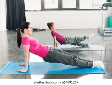 mother and adorable daughter in pink shirts practicing yoga in gym