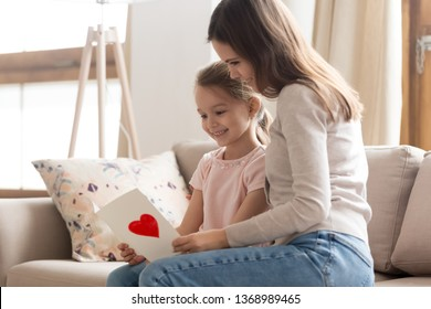 Mother and adorable daughter sitting on couch in living room read wishes text on handmade postcard, beautiful sisters looking at paper card, attentive kid made gift on international womens day concept