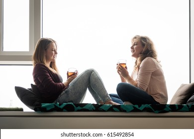 Mother and adult daughter chatting over tea at home