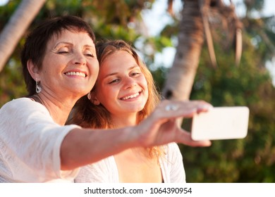 mother and adult daughter are doing selfie by mobile phone in summer