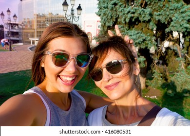 Mother and adult daughter are doing selfie in park in summer going crazy and laughing. Sunset light.Happy and positive emotions.Two friends on vacation.Parents and teenagers.Summer self-portrait