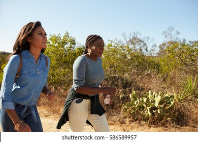 Mother And Adult Daughter Hiking Outdoors In Countryside