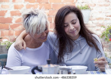 mother and adult daughter hugging each and having breakfast outdoors