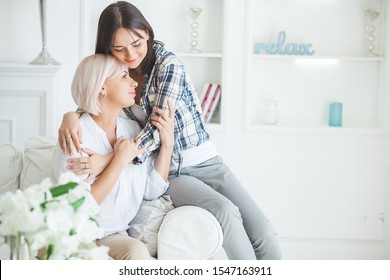 Mother and adult daughter together indoors. Happy family at home. Mid adult mom and her grown up daughet hanging out.