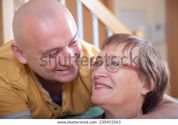 mother with adult son on  couch in  living room.