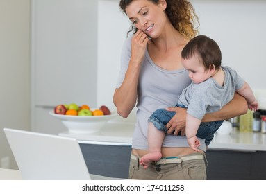 Mother answering cellphone while carrying baby boy in kitchen