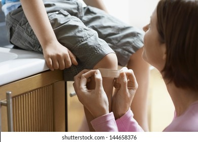 Mother applying bandage on her son's knee at home
