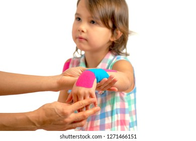 Mother applying kinisiology tape to her daughter injury hand